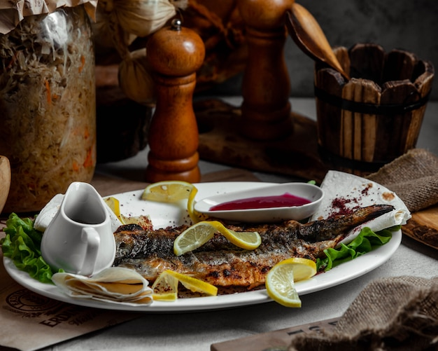 Grilled fish with lemon an tomato sauce.