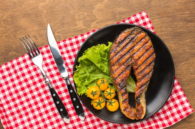 Grilled fish with lettuce flat lay