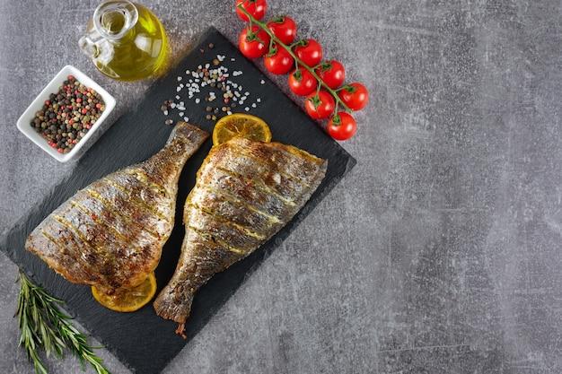 회색 배경에 검은 슬레이트 접시에 레몬, 로즈마리, 토마토, 올리브 오일, 향신료를 곁들인 구운 생선. 평면도, 복사 공간이 있는 평평한 위치.