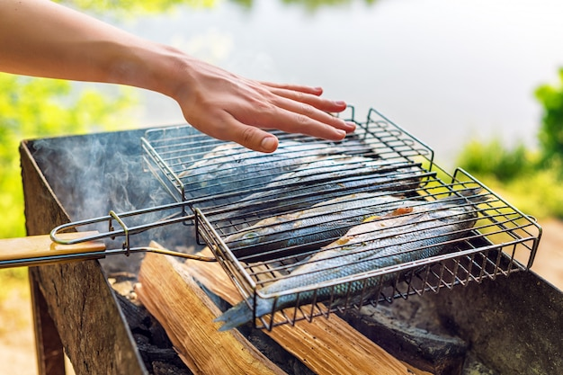 Grilled fish with spices on fire. fish barbeque in the garden outdoors, on a warm sunny day.