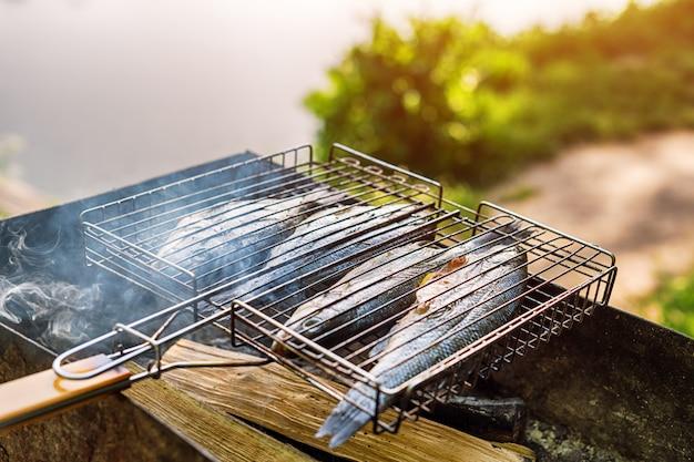 Жареная рыба со специями в огне. рыба барбекю в саду на открытом воздухе, в теплый солнечный день.