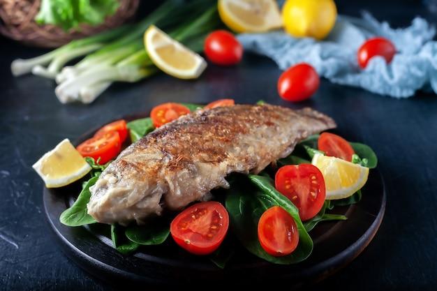 나무 보드 맛있고 가벼운 저녁 식사에 토마토 시금치와 생선 구이