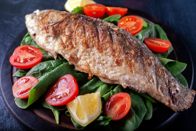 Grilled fish with tomatoes spinach on a wooden board delicious and light dinner