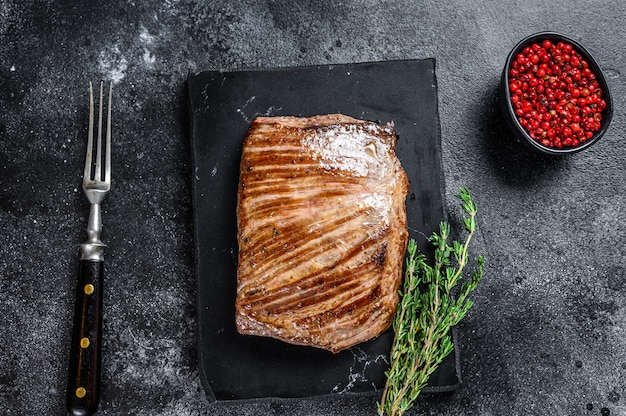 Grilled flank beef meat steak on a marble board