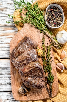 Grilled flank steak on a chopping board with seasonings and spices. white background. top view.