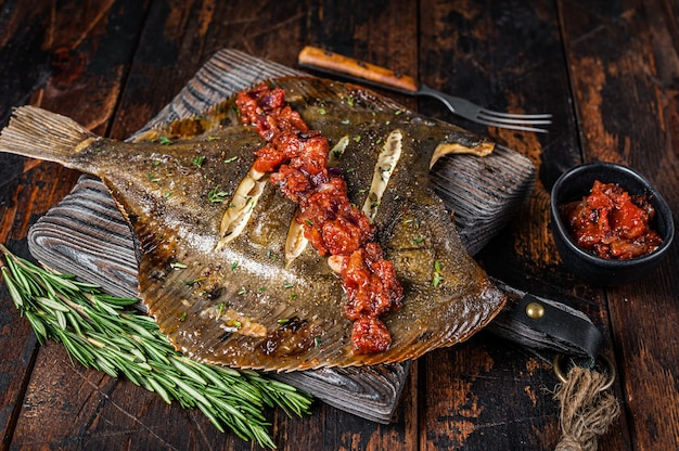 Grilled flounder or plaice with  tomato sauce on wooden cutting board. dark wooden background. top view.