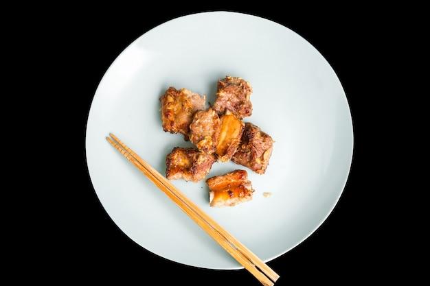 구운 신선한 돼지 갈비와 마늘, 후추를 둥근 접시에 섞는다