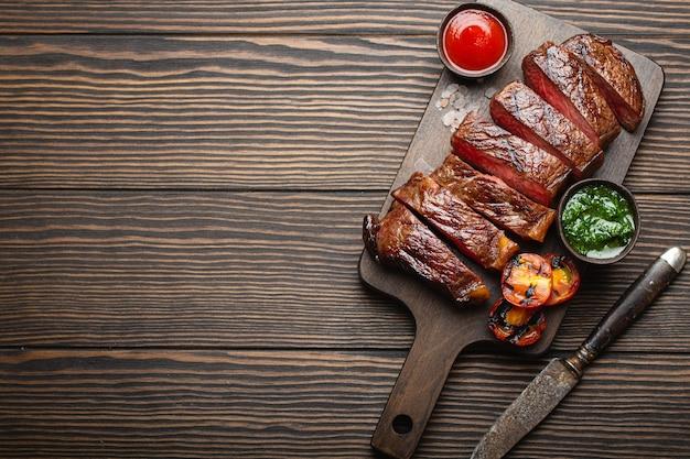 Жареный / жареный и нарезанный стейк из мраморного мяса с вилкой, помидорами, разными соусами на деревянной разделочной доске, вид сверху, крупный план с пространством для текста, деревенский фон. концепция стейка из говядины