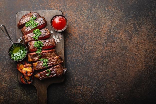 Жареный / жареный и нарезанный стейк из мраморного мяса с вилкой, помидорами, различными соусами на деревянной разделочной доске, вид сверху, крупный план с пространством для текста, деревенский каменный фон. концепция стейка из говядины