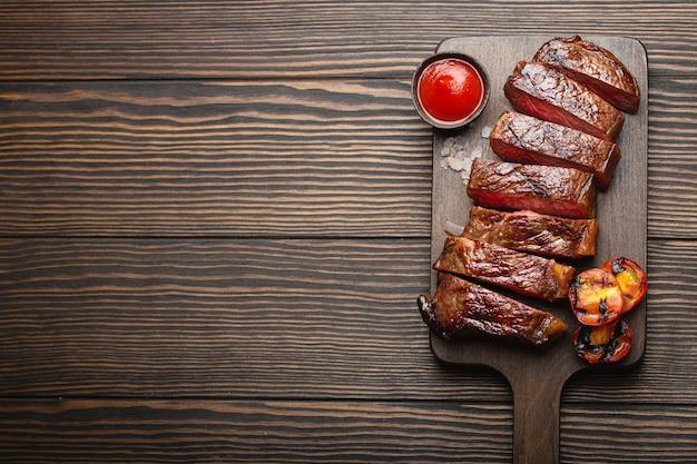 Жареный / жареный и нарезанный стейк из мраморного мяса с вилкой, помидорами, томатным соусом / кетчупом на деревянной разделочной доске, вид сверху, крупный план с пространством для текста, деревенский фон. концепция стейка из говядины