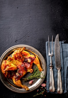 Grilled fried roast chicken tabaka with thyme and garlic