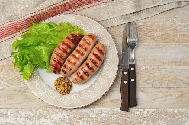 Жареная колбаса на гриле с листьями салата и перцем