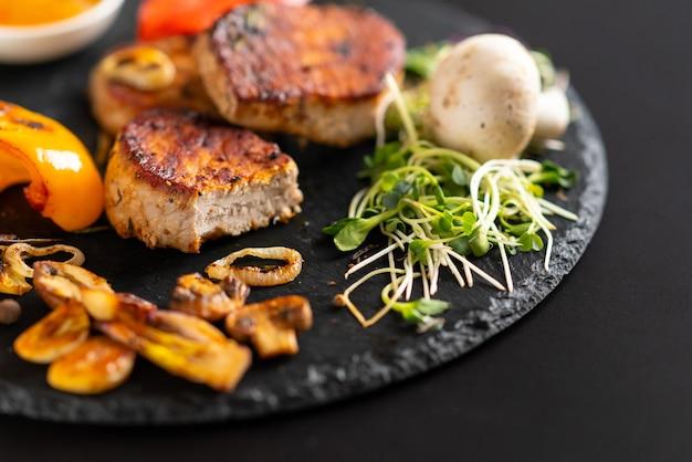 콩나물을 곁들인 구운 마늘 정향과 돼지 고기 등심 구이 부드러운 메달리온이 소박한 검정 접시 또는 보드에 제공됩니다.