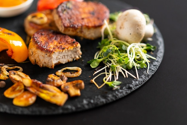 Grilled garlic cloves with sprouts and grilled tender medallions of pork fillet served on a rustic black plate or board