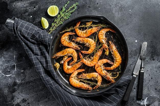巨大なエビのグリル、エビのニンニク、レモン、スパイスの鍋。黒い表面。上面図