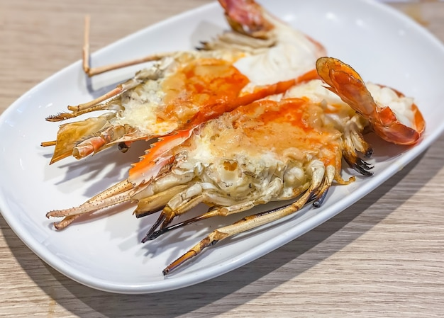 Grilled giant river prawn on white dish with spicy seafood sauce. popular thai food on wooden table as background