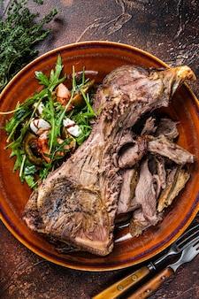 Жареное мясо козьей или баранины на гриле в деревенской тарелке с салатом. темный фон. вид сверху.