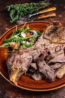 Запеченная на гриле козья или баранина лопатка в деревенской тарелке с салатом