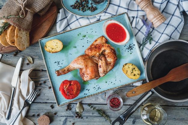 Grilled half chicken on blue plate