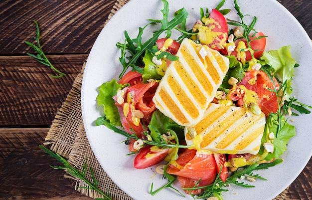 Салат из сыра халлуми на гриле с соленым лососем, помидорами и зеленью. здоровая пища на тарелке на деревянных фоне. вид сверху, баннер