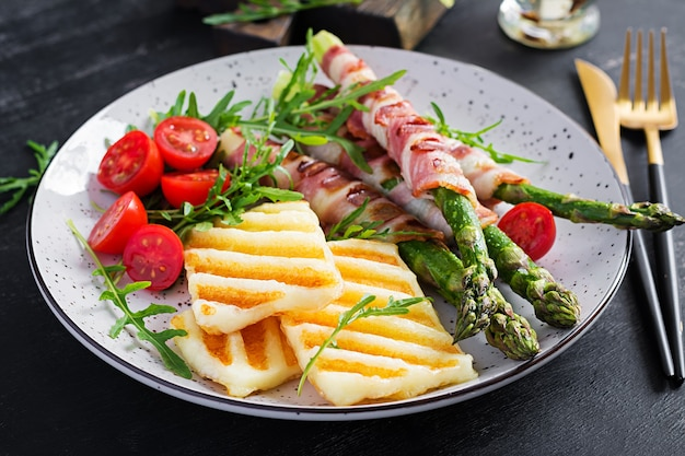 Салат из сыра халлуми на гриле с помидорами и спаржей в полосках бекона на тарелке на темном фоне. здоровая пища.