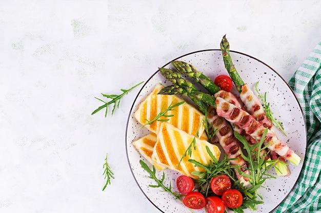 Салат из сыра халлуми на гриле с помидорами и спаржей в полосках бекона на тарелке на светлом фоне. здоровая пища. вид сверху, плоская планировка