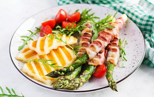 Салат из сыра халлуми на гриле с помидорами и спаржей в полосках бекона на тарелке на светлом фоне. здоровая пища.