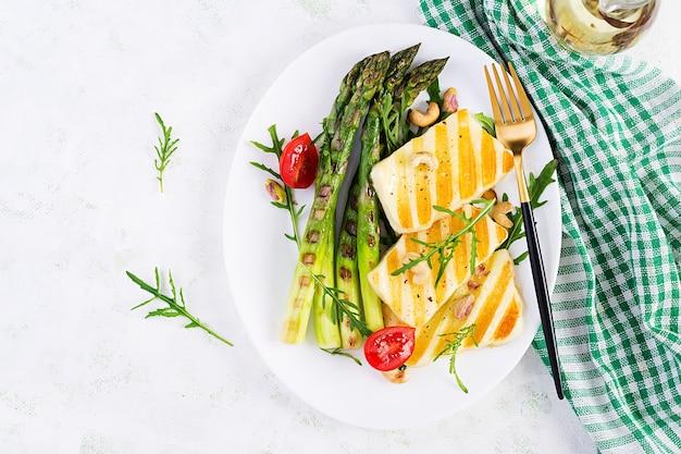 Салат из сыра халлуми на гриле с помидорами и спаржей на тарелке на светлом фоне. здоровое вегетарианское питание. вид сверху