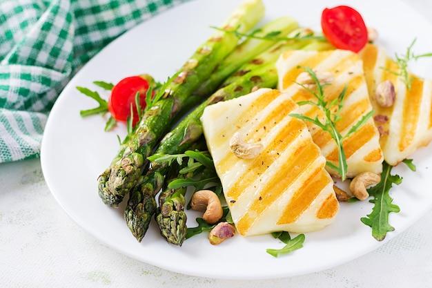 Салат из сыра халлуми на гриле с помидорами и спаржей на тарелке на светлом фоне. здоровое вегетарианское питание.