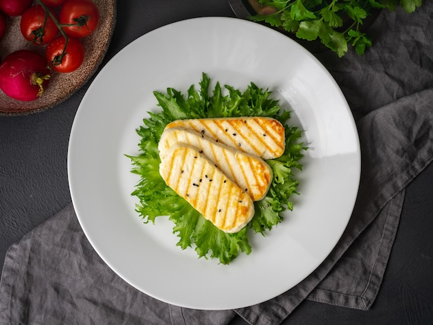 Grilled halloumi, fried cheese with  lettuce salad.  balanced diet, white plate on dark