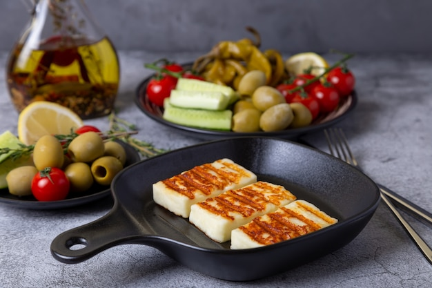 Grilled haloumi cheese on a black pan with olives, tomatoes, cucumbers and pepperoni. close-up.