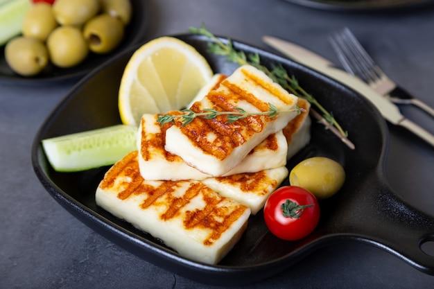 올리브, 토마토, 오이, 페퍼로니와 함께 검은 팬에 구운 haloumi 치즈. 확대.