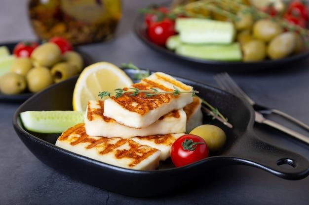 オリーブ、トマト、きゅうり、ペパロニを添えた黒い鍋でのハルーミチーズのグリル。閉じる。