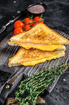 커팅 보드에 구운 햄과 치즈 샌드위치