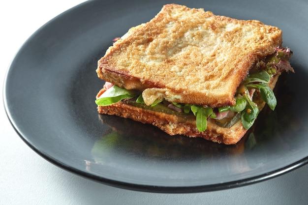 黒いプレートにハムとチーズのグリルサンドイッチ
