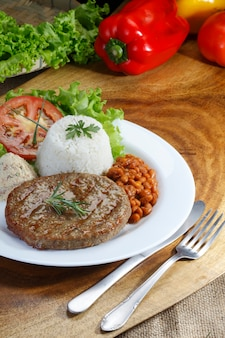 Grilled hamburger meat with rice, beans and salad