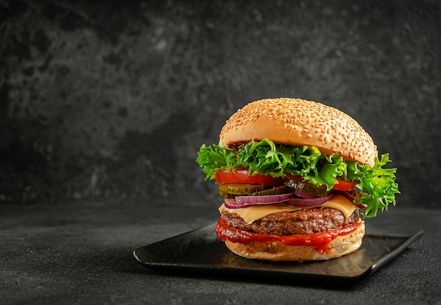 Grilled hamburger with beef patty, onion,tomato,salad, pickled cucumber and cheddar cheese