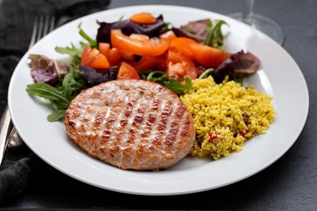 세라믹 배경에 흰색 접시에 시리얼과 샐러드와 구운 햄버거