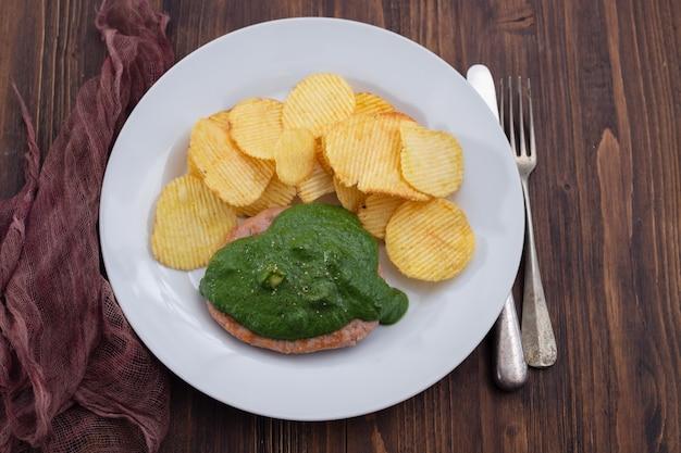 Гамбургер на гриле с зеленым соусом и картофельными чипсами на белой тарелке