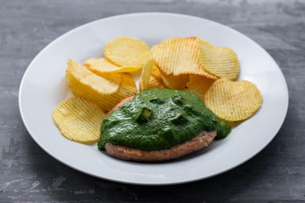 白いプレートにグリーンソースとポテトチップスを添えたハンバーガーのグリル