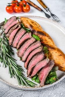 Grilled homemade rib eye steak sandwich with sliced roast beef, arugula.