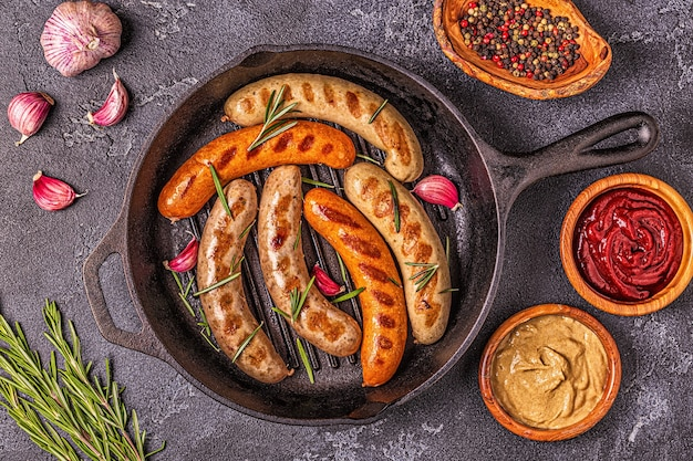 Grilled homemade sausages in a pan, top view.