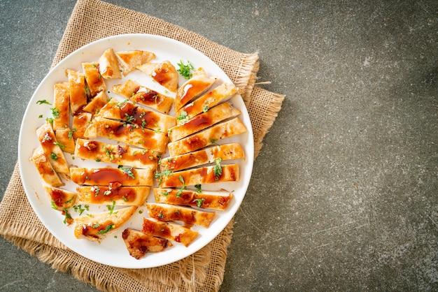 Жареная куриная грудка в меде, нарезанная на белой тарелке