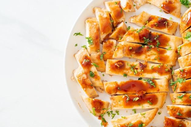 Жареная куриная грудка с медом, нарезанная на белой тарелке