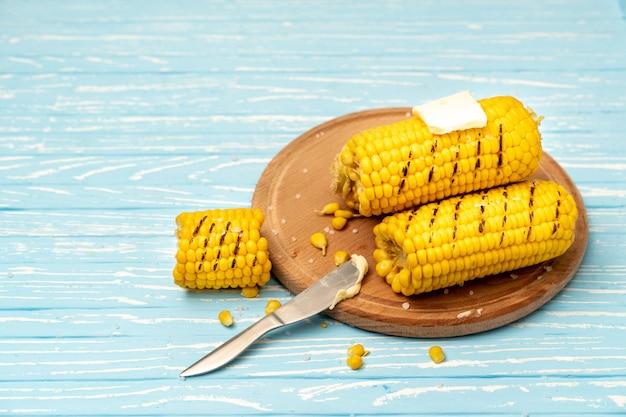 焼きトウモロコシの穂軸は丸いカッティングボードプレート青い木製テーブル背景にあります。テキストのスペースをコピーします。