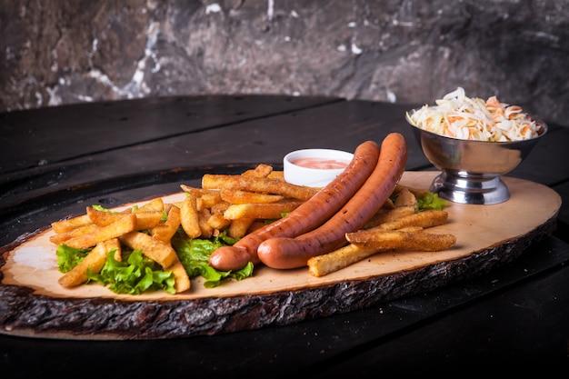Жареные сосиски, картофель фри, кетчуп и салат на разделочной доске