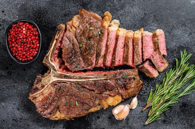 Жареный на гриле итальянский флорентийский или стейк из говядины на косточке. черный фон. вид сверху.