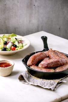 Жареные итальянские колбаски сальсичча в чугунной сковороде с томатным соусом и тарелкой салата из свежих овощей на белом мраморном столе. сбалансированный ужин