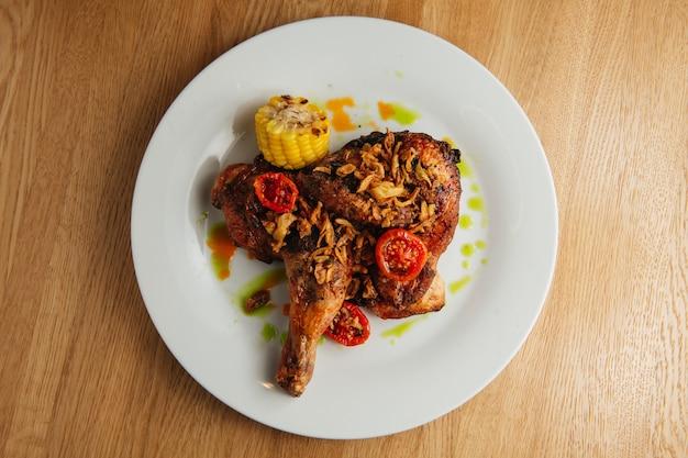 흰색 접시에 황금 갈색 껍질과 구운 된 육즙 치킨