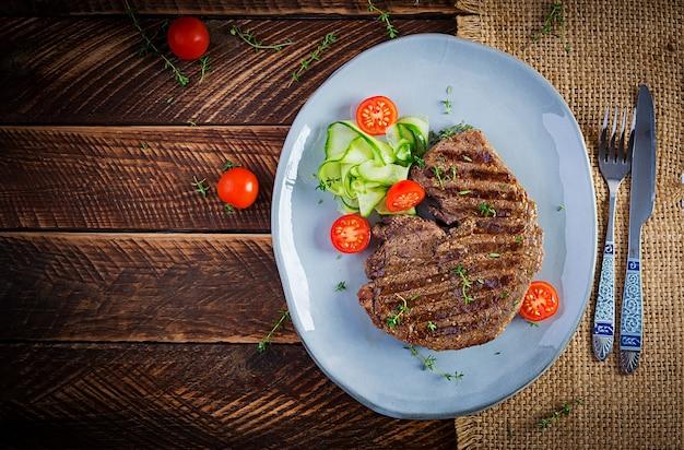 Сочный стейк на гриле из говядины средней прожарки со специями и свежим салатом. вид сверху, сверху, плоская планировка